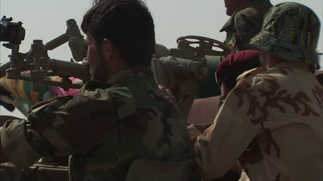 stockvideo's en b-roll-footage met exterior shows peshmerga forces on fixed canon troops ready heavy gun shells lined up - goede staat