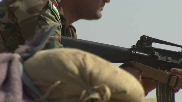 exterior shows peshmerga troops on front line looking down sights of m16 assault rifle in bunker - m16 stock videos & royalty-free footage