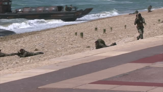 exterior shows royal marine drill beach landing in reference to normandy landings, amphibious vehicles hit land from water and marines storm out to... - royal marines stock videos & royalty-free footage