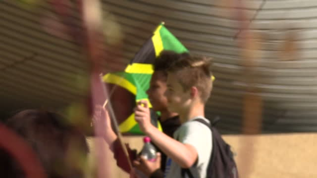 vídeos y material grabado en eventos de stock de exterior side view shot two young boys wave jamaican flags at the olympic stadium for the world athletics championships 2017, in support of usain... - jamaiquino