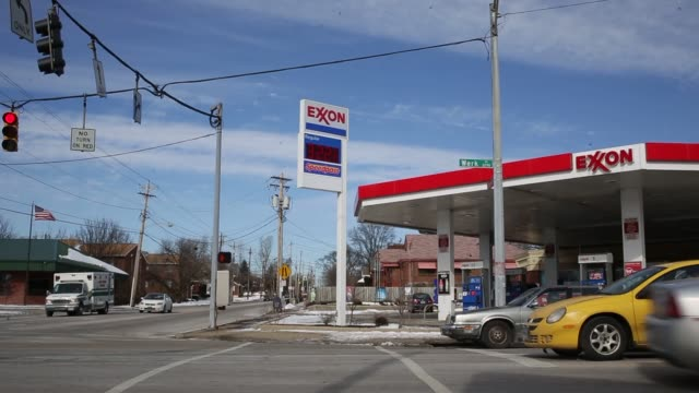 exterior signage shots of an exxon gas station in cincinnati ohio traffic passes by and motorists fill up their vehicles at an exxon gas station in... - exxon stock videos & royalty-free footage