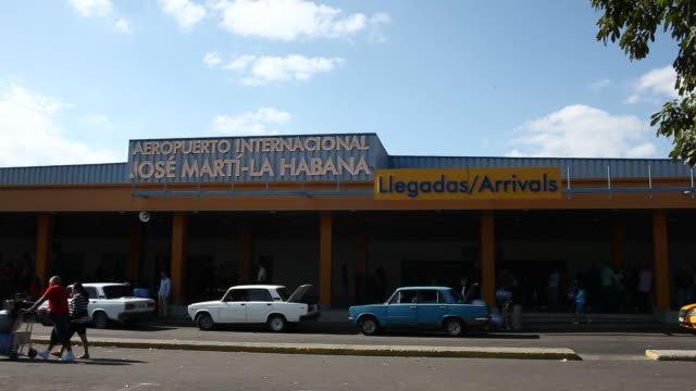 vidéos et rushes de exterior signage shots of the jose marti international airport in havana cuba on a sunny day exterior shots of passengers unloading their luggage... - décharger