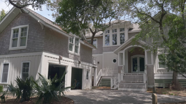 exterior. slomo. dolly-in on large two-story luxury marshside bald head island beach house with separate above garage apartment shaded by trees on sunny summer day. - bald head island stock videos and b-roll footage