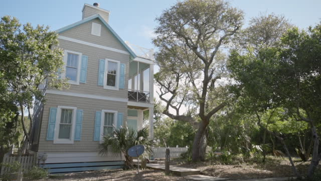 exterior. slomo. side view of two-story luxury bald head island beach house surrounded by wooded area, empty tree swing sways in the breeze on sunny summer day. - patio stock videos & royalty-free footage
