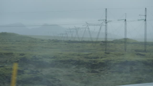 stockvideo's en b-roll-footage met exterior slow motion driving shots through rural iclandic scenery past a wind farm, open landscapes and sea on 9 september 2020 in iceland - clean