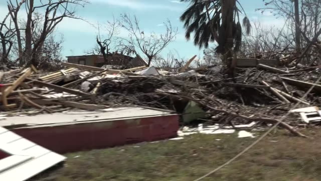 exterior slow tracking views of destruction caused by hurricane dorian, including wreckage of houses, people walking and fallen trees on 6 september... - バハマ点の映像素材/bロール