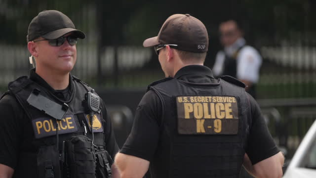 stockvideo's en b-roll-footage met exterior slowmotion shots of secret service personnel standing guard outside the white house perimeter fence >> on november 06 2017 in washington dc - geheime dienstagent