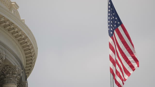 Exterior slowmotion shots of the United States flag fluttering in the breeze outside the US Capitol and various architectural features of the Capitol...