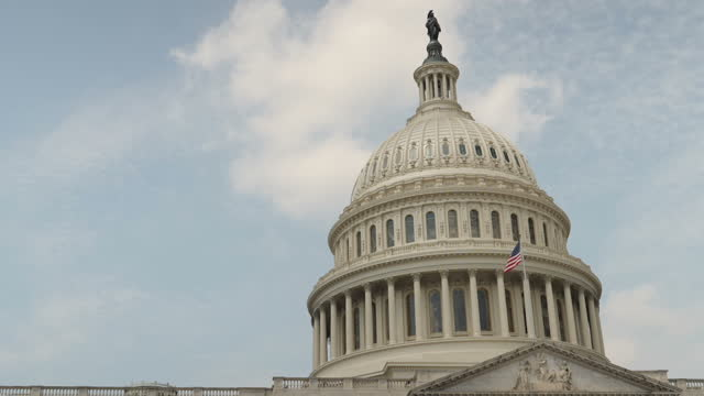 vídeos de stock e filmes b-roll de exterior slowmotion shots of the us capitol including views of the united states flag blowing in the breeze and the capitol building reflected in the... - capitol hill