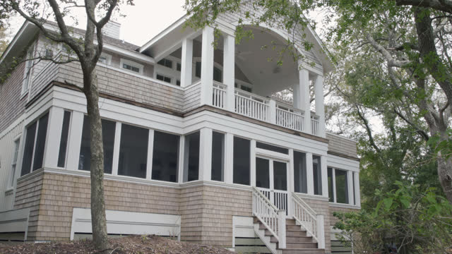 exterior. static view of two-story screened-in porches of luxury, marshside bald head island beach house on a cloudy summer day. - column stock videos & royalty-free footage