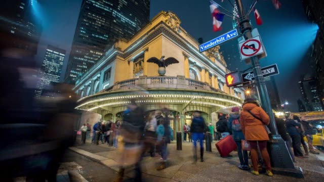 Exterior time lapse shots of tourists and commuters walking through Grand Central Terminal at night with the signage lit up in New York City US on...