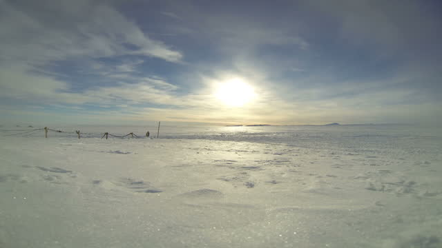 Exterior timelapse shot of the sun shining above the Antarctic landscape with occasional snowmobile and figures seen in the distance Walking With The...