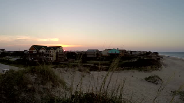 exterior timelapse shots of the sun setting over a beach at nags head north carolina with dunes on the beach and luxury beachfront houses on july 13... - carolina beach stock videos and b-roll footage