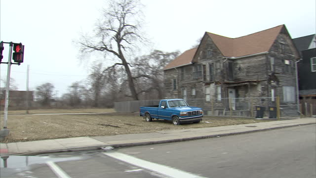 vidéos et rushes de exterior tracking shot from vehicle along suburban detroit streets with residential housing large open green spaces abandoned housing and buildings... - délabré
