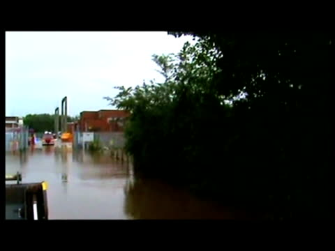 exterior tracking shot of flooded electrical substation pylons through fence exterior shots of fire and rescue services exterior shots of hose... - water pumping station stock videos & royalty-free footage