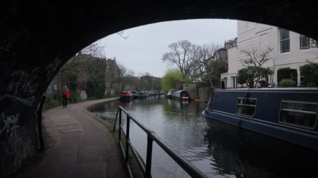 exterior tracking shots of a canal boat on regents canal as it travels under a low bridge alongside houses and other moored boats on 18th march... - other stock videos & royalty-free footage