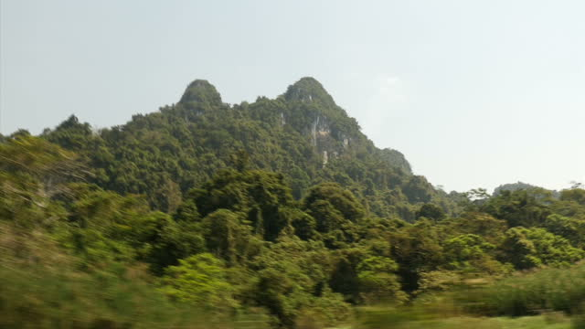 Exterior travelling shot past rich verdant foliage mountains and a river in Cuc Phuong National Park on February 23 2015 in Hanoi Vietnam