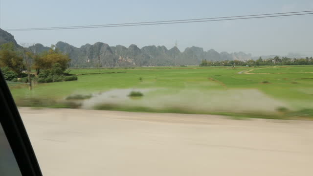 Exterior travelling shots through Cuc Phuong National Park past rice paddy fields with mountains in the distance and forests on February 23 2015 in...