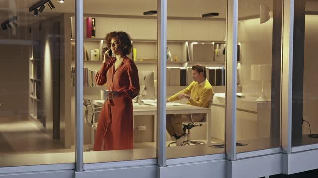 vidéos et rushes de vidéo extérieure par fenêtre à designer féminin utilisant le téléphone dans le bureau moderne tard dans la nuit - agence de design