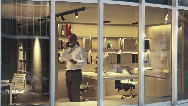 Vídeo exterior através da janela para arquiteto masculino em meados dos anos 50 usando telefone em escritório moderno tarde da noite