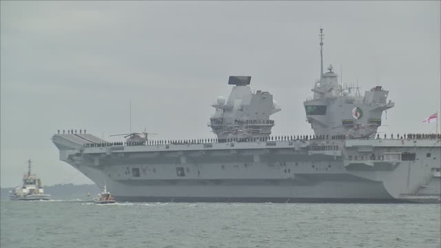 stockvideo's en b-roll-footage met exterior view of aircarft carrier hms queen elizabeth departing portsmouth navel base, for flight trials off the coast of north america on 18th... - navel