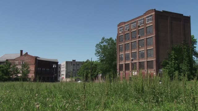 exterior view of an abandoned warehouse currently for lease or sale / 6 story warehouse building in patterson nj abandoned warehouse on may 19 2012... - 賃貸契約点の映像素材/bロール