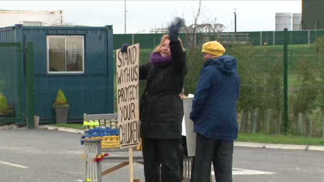 vidéos et rushes de exterior view of anti fracking campaigners holding placards and banners and flags outside the fracking plant site on october 12 2018 in blackpool... - lancashire