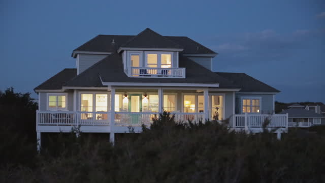 exterior. view of back porch and balcony of two-story luxury seaside bald head island beach house from the dunes at dusk. - bald head island stock videos and b-roll footage