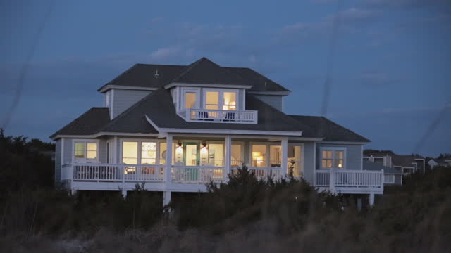 exterior. view of back porch and balcony of two-story luxury seaside bald head island beach house from the dunes at dusk. - back lit stock-videos und b-roll-filmmaterial