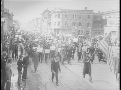 exterior view of bethlehem steel mill / workers marching with american flag leading / montage of workers returning to work carrying lunches / new... - anno 1941 video stock e b–roll