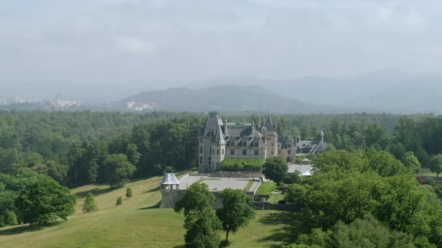 WS AERIAL POV Exterior view of Biltmore Estate with surrounded by forest area / Asheville, North Carolina, United States