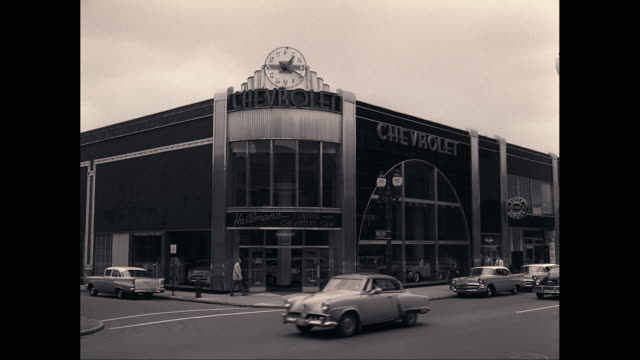 ws exterior view of chevrolet car showroom with sign, cars moving on street in foreground / detroit, michigan, united states - デトロイト点の映像素材/bロール