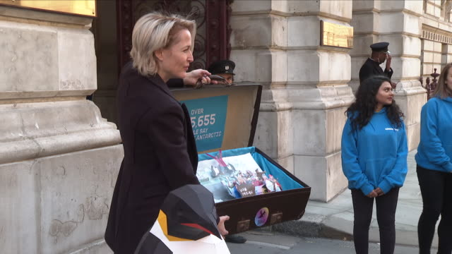 Exterior view of Gillian Anderson posing for the press outside the Foreign and Commonwealth Office holding up the suitcase containing a petition...
