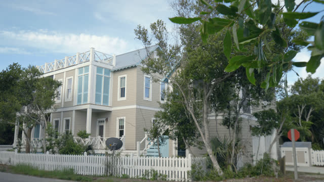 exterior. view of luxury two-story bald head island beach house with rooftop balcony on a sunny summer day. - column stock videos & royalty-free footage