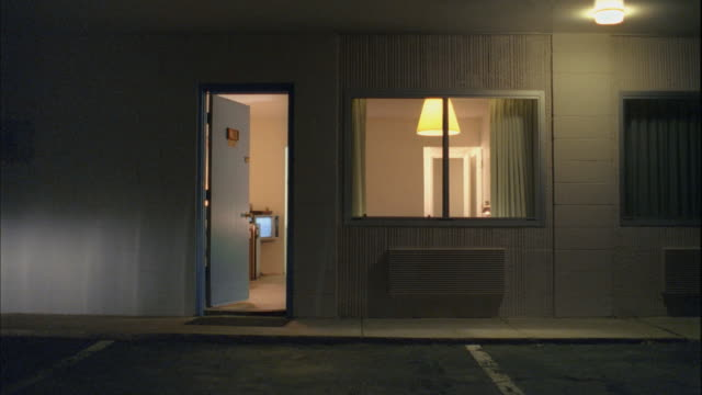 ms, exterior view of motel room with doors open at night, tonopah, nevada, usa - freizeitelektronik stock-videos und b-roll-filmmaterial