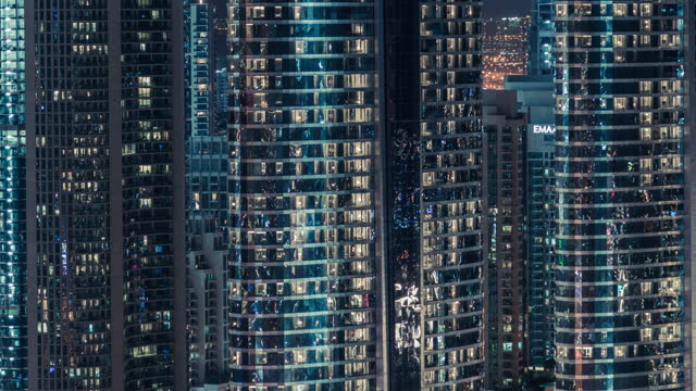 t/l pan exterior view of skyscraper in dubai at night - middle east stock videos & royalty-free footage