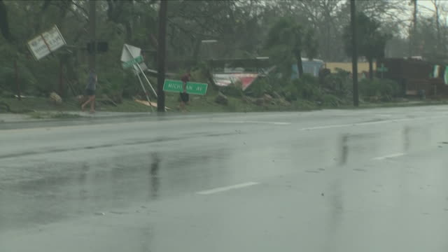 exterior view of someone walking along with a michigan ave street sign under their arm in the aftermath of hurricane michael and debris in the road... - looting stock videos & royalty-free footage