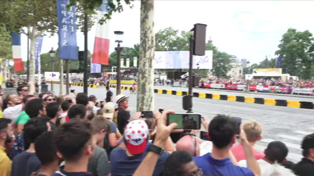 Exterior view of the crowd watching the Tour de France peloton cycling past on on the Avenue des ChampsÉlysée and then the French Red Arrows' The...
