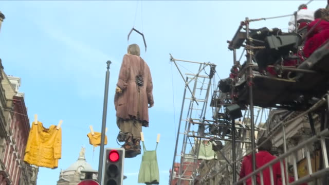 vídeos de stock e filmes b-roll de exterior view of the giant man oversized giant marionette being swung through the air into place from a crane in liverpool town centre, including... - marionete