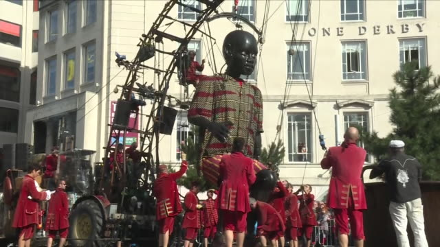 vídeos de stock e filmes b-roll de exterior view of the little boy giant oversized giant marionette being stood up by puppet operators and then walking through liverpool town centre on... - marionete