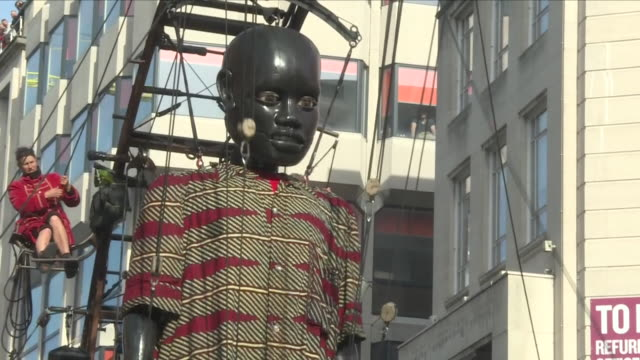 vídeos de stock e filmes b-roll de exterior view of the little boy giant oversized giant marionette walking through liverpool town centre, including views of the puppet operators... - marionete