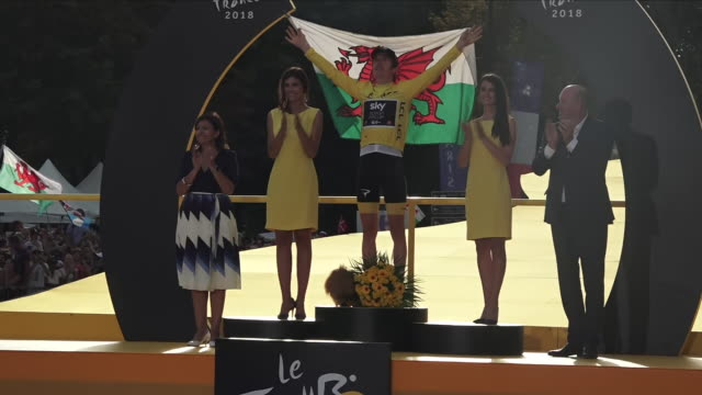 exterior view of tour de france winner geraint thomas celebrating on the winners podium on the avenue des champsélysée and holding up a wales flag... - ツール・ド・フランス点の映像素材/bロール