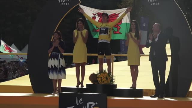 Exterior view of Tour de France winner Geraint Thomas celebrating on the winners podium on the Avenue des ChampsÉlysée and holding up a Wales flag...