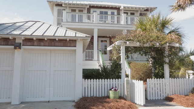 exterior. view of two-story luxury seaside bald head island beach house with flower-covered front gate on a breezy sunny summer day. - bald head island stock videos and b-roll footage