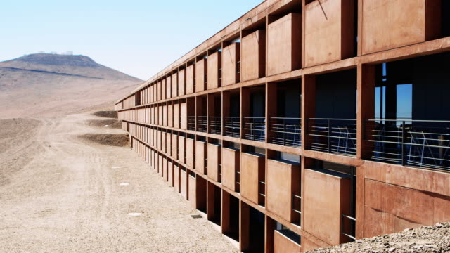 ws exterior view of vlt residencia with telescopes in distance at paranal observatory / chile - four objects stock videos & royalty-free footage