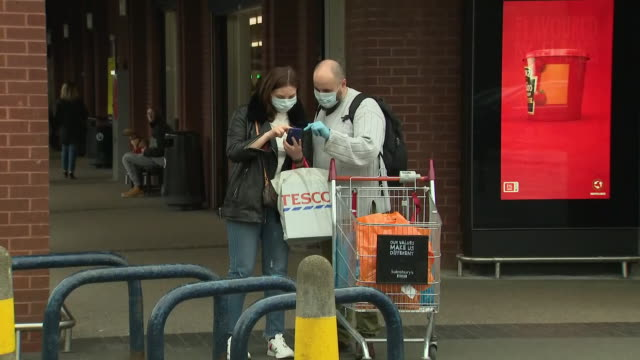 exterior views of a couple wearing face masks, standing outside a chiswick supermarket after having been shopping on 15 march 2020 in london, united... - couple relationship stock videos & royalty-free footage