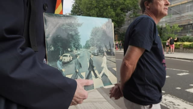 exterior views of a group of tourists and fans recreating the iconic cover photo of the beatles album abbey road on the 50th anniversary of the photo... - zebra crossing stock videos & royalty-free footage