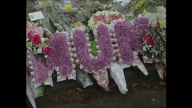 exterior views of a people looking at floral tributes laid to the victims of the dunblane massacre, including close ups of written messages on 16... - ダンブレーン点の映像素材/bロール