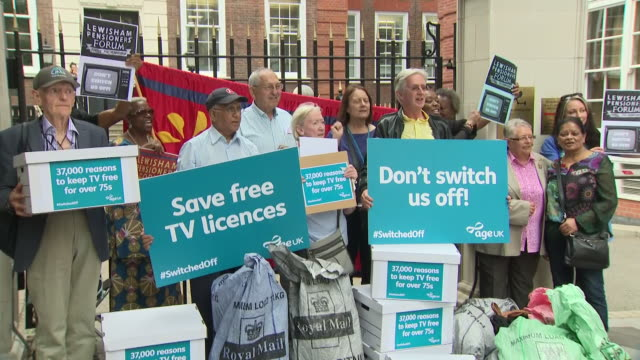 exterior views of a protest by pensioners, holding don't switch us off placards and handing over a petition over the tv licence fee for over 75's... - bbc bildbanksvideor och videomaterial från bakom kulisserna