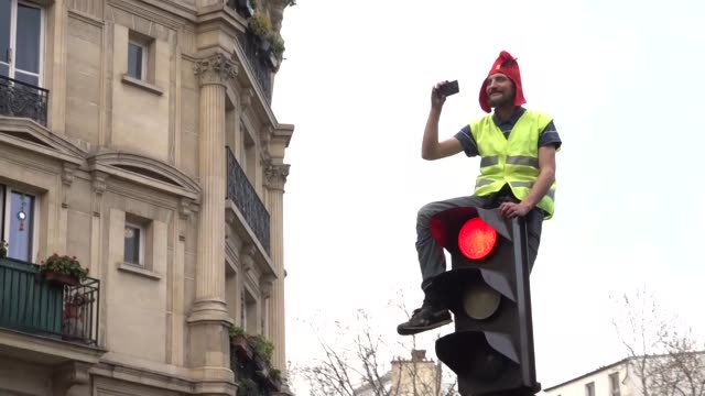 Exterior views of a single yellow vest protester wearing a red cap or bonnet rouge sitting on a traffic light in the air taking moble phone footage...